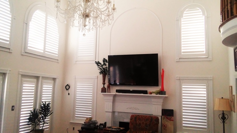 Las Vegas great room with wall-mounted TV and arched windows.